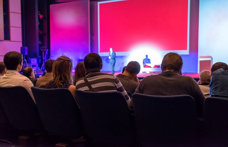 speaker on stage giving presentation